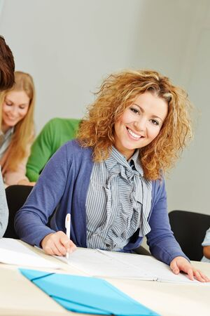 taking notes: Happy woman learning in study course and taking notes