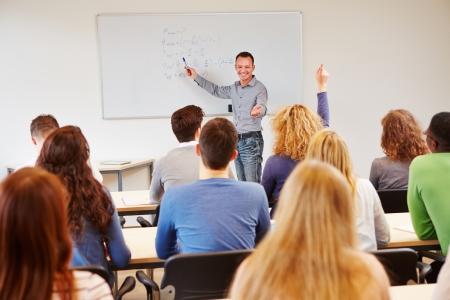 teacher: Estudiante levanta la mano en clase de la escuela y recibiendo llamadas por el maestro Foto de archivo