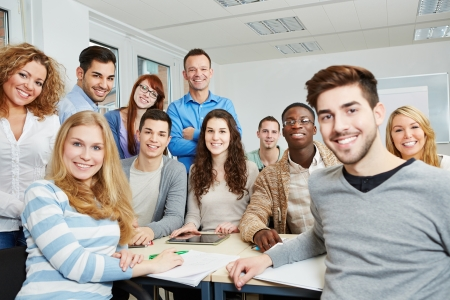 Group of happy students with teacher and tablet computer in class photo