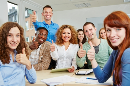 training group: Successful students holding their thumbs up with teacher in classroom
