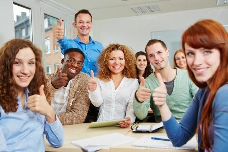 training: Succesvolle studenten met hun duimen omhoog met leraar in de klas Stockfoto