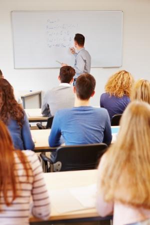 Teacher writing financial mathematics formulas on whiteboard in university photo