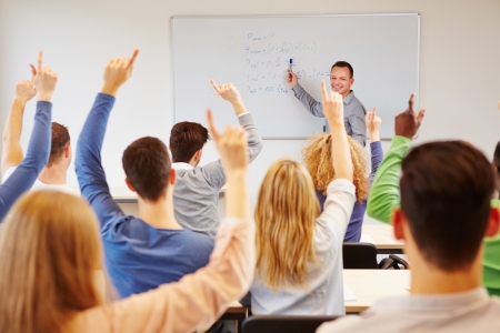 university classroom: Students lifting hands in college class with teacher on whiteboard Stock Photo