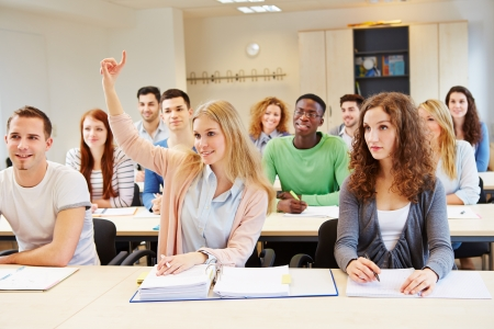high school girl: Diligent female student lifting hand in university seminar classroom Stock Photo
