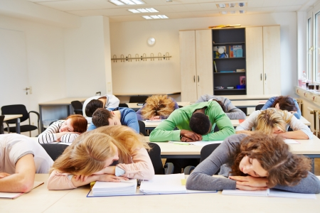 Many tired students sleeping in classroom with their heads on the table photo
