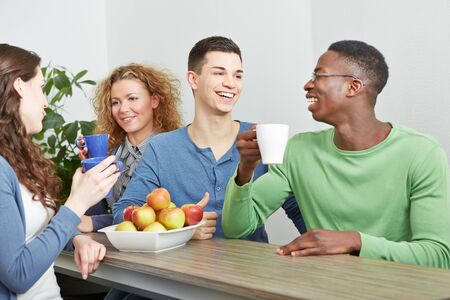 office break: Many smiling colleagues drinking coffee in break room