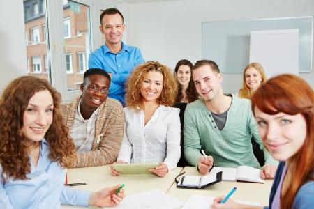 profesores: Maestro con sus estudiantes felices en un aula curso universitario Foto de archivo