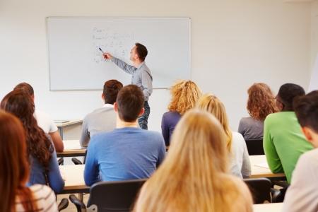 classroom teacher: Students listening to teacher in class on a whiteboard Stock Photo