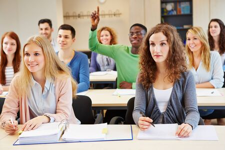 African student lifting hand in classroom of university seminar photo