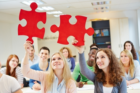 Students solving jigsaw puzzle as a team in university class photo