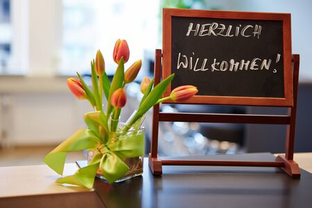 willkommen: Blackboard with german Herzlich Willkommen welcome slogan Stock Photo