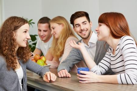 taking a break: Happy students taking a coffee break in break room