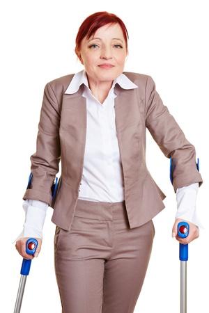 paraplegia: Smiling business woman walking with two crutches Stock Photo