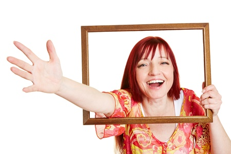 Happy smiling woman reaching through empty picture frame Stock Photo - 18919847