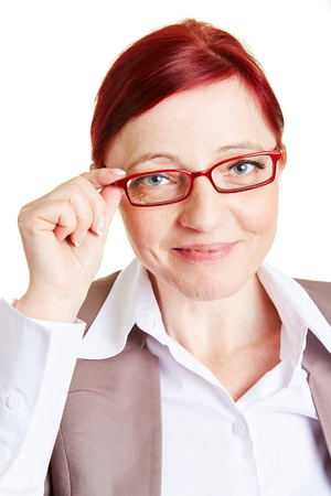farsighted: Best ager business woman smiling and touching spectacles of her glasses