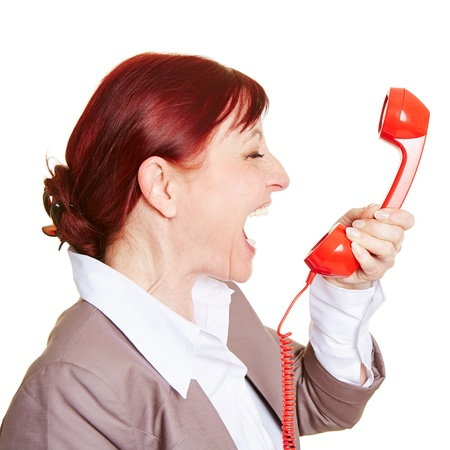 rant: Angry business woman screaming loudly in a red phone receiver