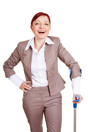 Happy best ager business woman standing with crutches photo