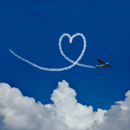 written communication: Skywriter paints a heart in the blue sky as symbol for love Stock Photo