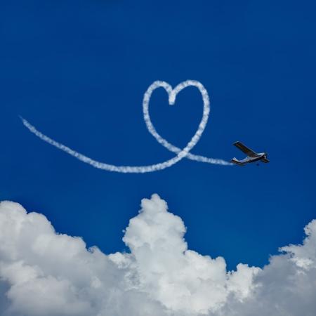 Skywriter schildert een hart in de blauwe hemel als symbool voor de liefde Stockfoto