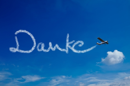 Airplane painting the German word Danke (Thanks) in the sky Stock Photo