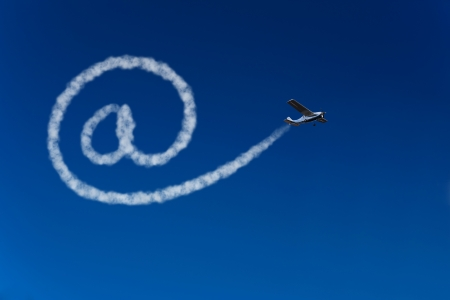 Skywriting airplane painting an at sign in the blue sky photo