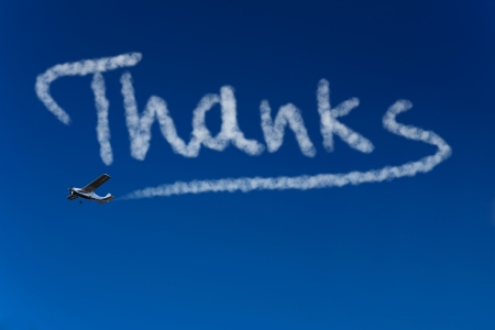 to say: Skywriter writing the word Thanks in the blue sky Stock Photo