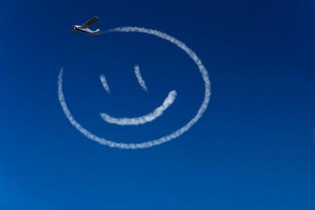 cara sonriente: Avión Skywriter pinta una carita feliz en el cielo azul Foto de archivo