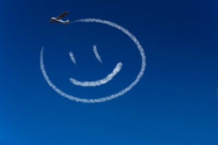 happiness symbol: Skywriter airplane paints a happy smiley in the blue sky