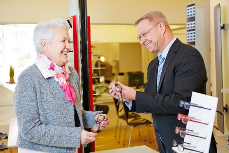 Optician helping senior woman finding new glasses photo