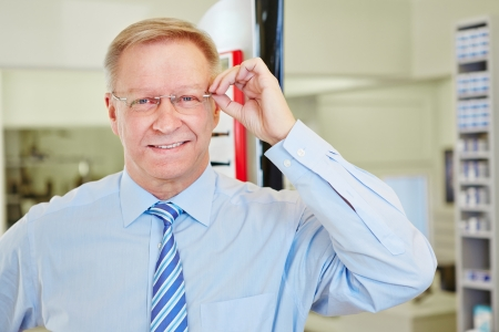 rimless: Smiling elderly man with new glasses at the optician Stock Photo