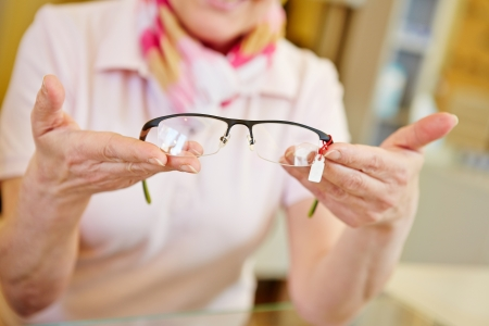 Hands of optician offering new fashionable glasses photo