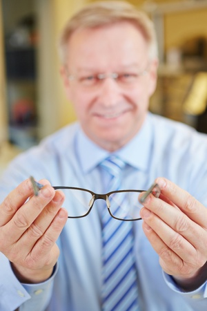 ophthalmic: Happy smiling senior optician holding new glasses at consultation Stock Photo