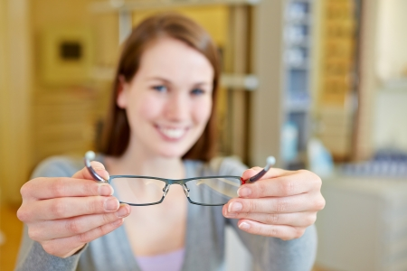 Young woman holding new glasses in optician store photo