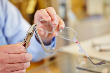 align: Hand of optician fixing glasses with bending pliers Stock Photo