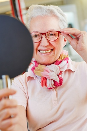 Nearsighted senior woman with new glasses looking into mirror at optician photo