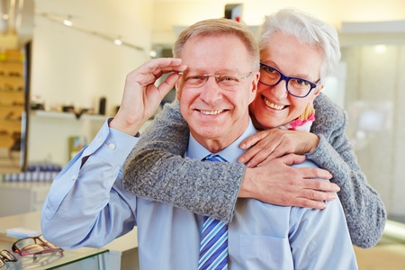 Happy senior couple with new glasses at optician retail store photo
