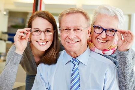 man with glasses: Happy family buying new glasses at optician retail store