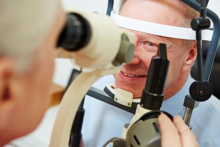 slit: Hombre mayor en la �ptica mirando en l�mpara de hendidura para conseguir su c�rnea examinada