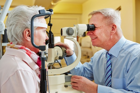 eye patient: Ophthalmologist examing cornea of senior woman with slit lamp