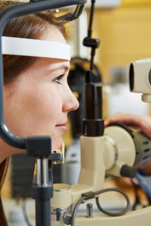 provision: Young woman at eye examination with slit lamp at optician