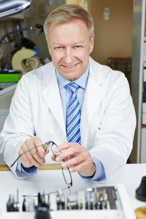 bracing: Senior optician repairing glasses with pliers in a workshop