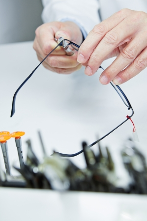 Workshop repair of glasses through hands of an optician photo