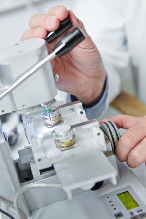 rimless: Hand of optician using drilling machine for rimless glasses