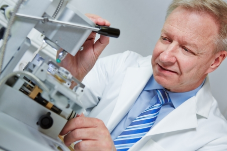 rimless: Optician drilling rimless glasses in his workshop Stock Photo