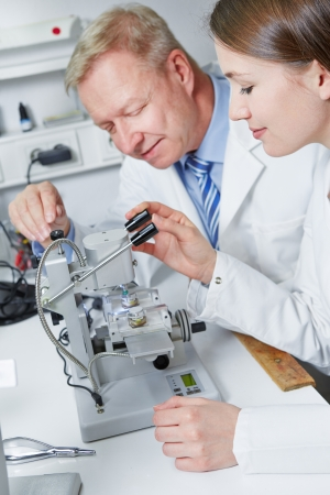 apprenticeship: Woman learning use of drilling machine in apprenticeship in optician workshop