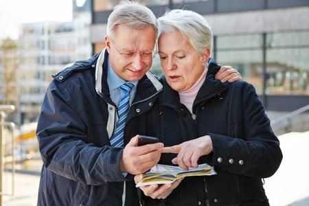 tour guide: Matrimonios de edad en calidad de turistas con el mapa y el smartphone en una ciudad Foto de archivo