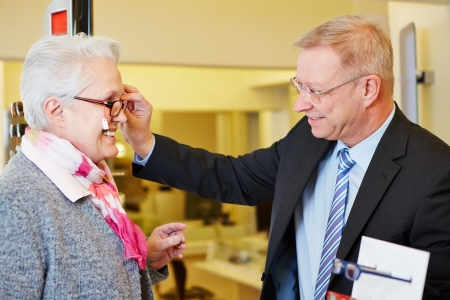 Elderly happy woman buying new glasses at optician store photo
