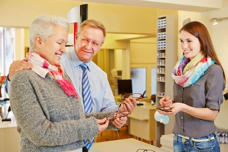 Happy senior couple buying new glasses at optician store photo