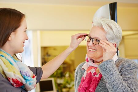 Young optician advising a senior woman for buying new glasses photo