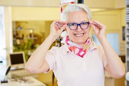 Happy senior woman with her new glasses at the optician photo